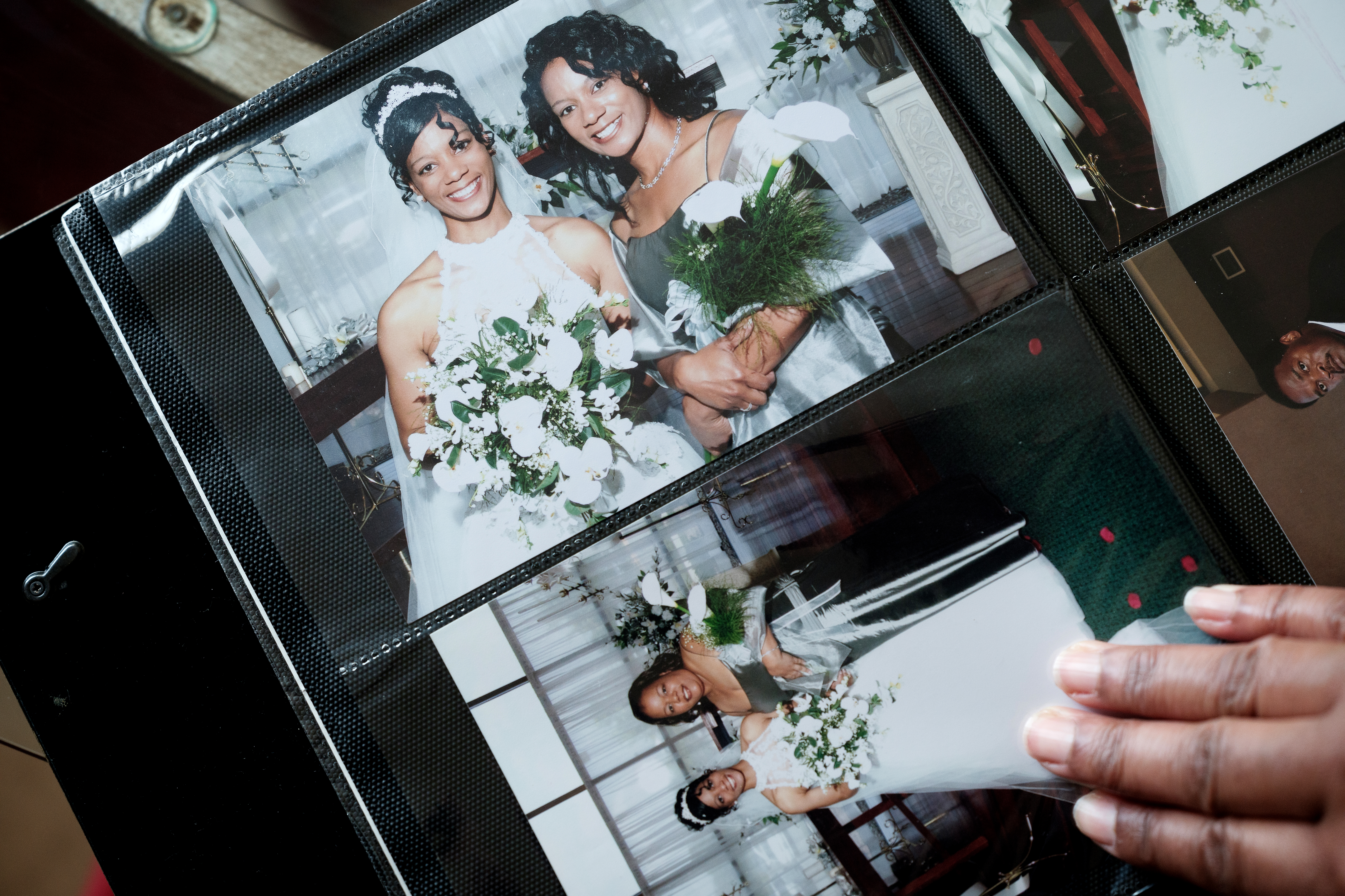 hand looking through photos of Kimberly Ketter and Shaun Rivers at wedding